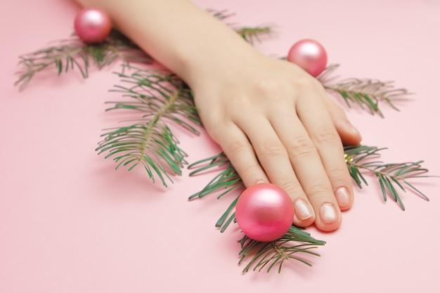 Schließen sie herauf schöne frauenhände, die einen weihnachtsbaumzweig mit rosa kugeln halten