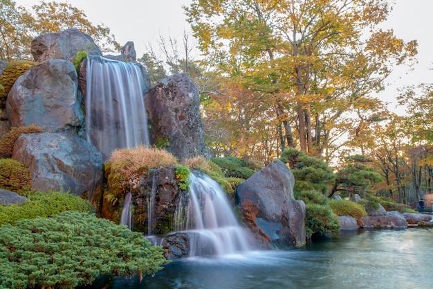 Schließen sie herauf schönes wasserfall- und waldänderungsfarbblatt im herbst bei japan.