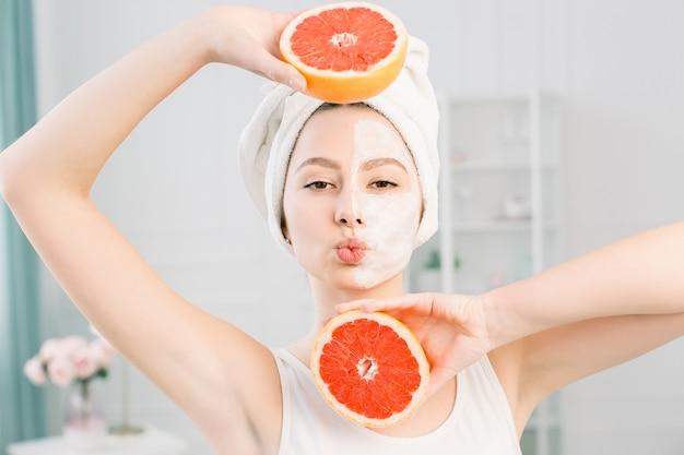 Schließen sie herauf schönheit frau mit perfekter haut nackt make-up halten grapefruit isoliert auf hellen raum, studio-porträt. konzept für kosmetische verfahren im gesundheitswesen. kopieren sie den speicherplatz