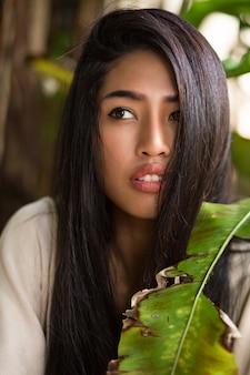Schließen sie herauf schönheitsporträt der asiatischen frau mit perfekter haut, die im tropischen garten aufwirft. gesunde haare, volle lippen.