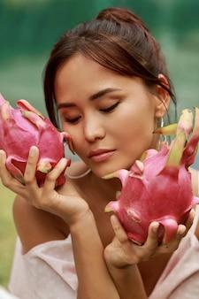 Schließen sie herauf schönheitsporträt der hübschen asiatischen frau mit drachenfrucht neben gesicht.