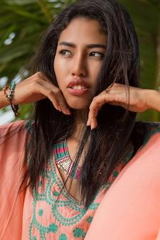 Schließen sie herauf schönheitsporträt der jungen asiatischen frau auf palme. perfekte haut. blick auf den ozean. sonnenuntergang.