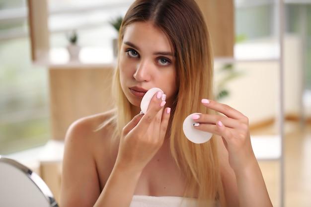Schließen sie herauf schönheitsporträt der schönen halbnackten frau, die gesichtscreme aufträgt.