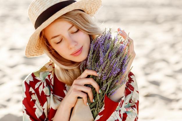 Schließen sie herauf schönheitsporträt des reizenden romantischen blonden mädchens, das perfekten geruch von lavendel genießt. hautpflege- und kosmetikkonzept. warme sonnenuntergangsfarben. geschlossene augen.