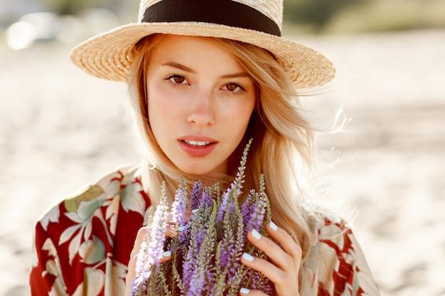 Schließen sie herauf schönheitsporträt des reizenden romantischen blonden mädchens, das perfekten geruch von lavendel genießt. hautpflege- und kosmetikkonzept. warme sonnenuntergangsfarben.