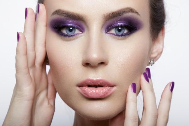 Schließen sie herauf schönheitsporträt einer frau, die die kamera betrachtet und lila make-up trägt