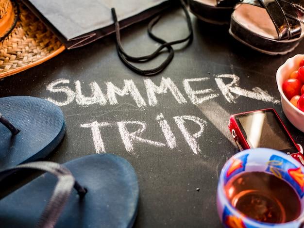 Schließen sie herauf schriftlichen text der sommerreise auf schwarzer tafel mit damenreisezubehör