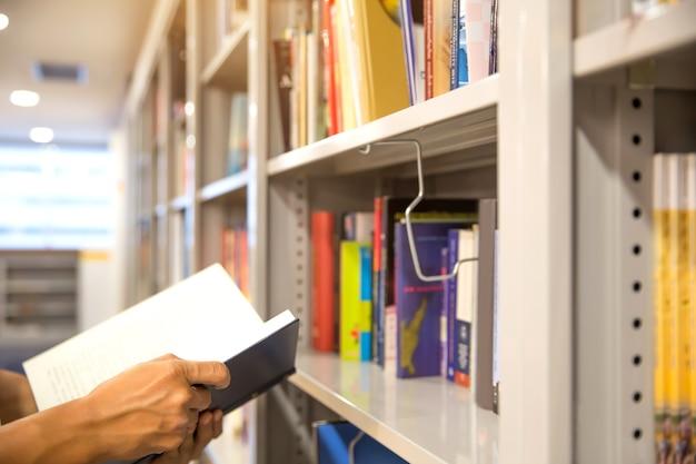 Schließen sie herauf schüler, der ein buch vom bücherregal in der bibliothek liest.
