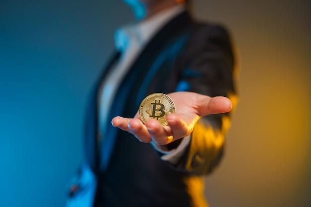 Schließen sie herauf schuss der geschäftsfrau im schwarzen anzug, der goldene münze lokalisiert auf hintergrund hält.