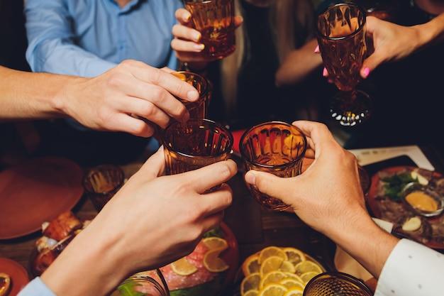 Schließen sie herauf schuss der gruppe von leuten, die gläser mit wein oder champagner anstoßen