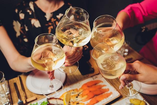 Schließen sie herauf schuss der gruppe von leuten, die gläser mit wein oder champagner vor bokeh hintergrund klirren. ältere menschen hände.