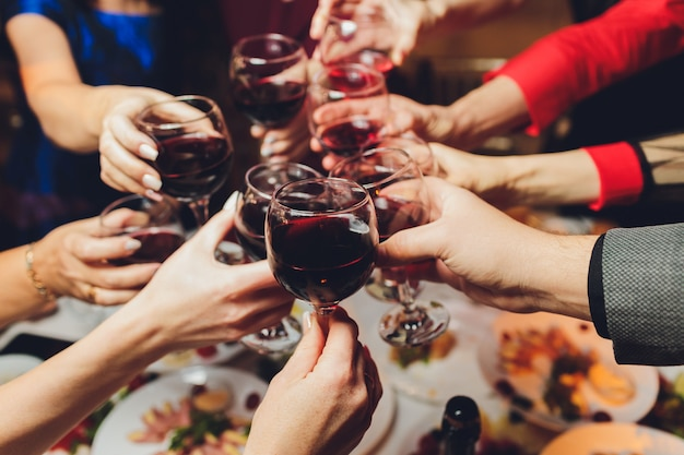 Schließen sie herauf schuss der gruppe von leuten, die gläser mit wein oder champagner vor bokeh hintergrund klirren