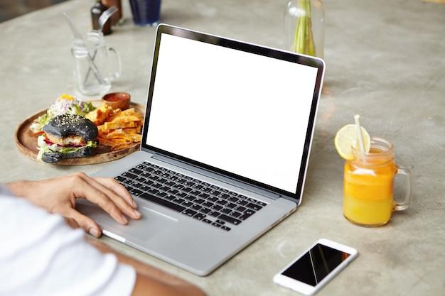 Schließen sie herauf schuss der hand des mannes auf touchpad des allgemeinen laptop-computers. kaukasischer student, der auf notebook-pc tastet und an seinem diplomprojekt arbeitet