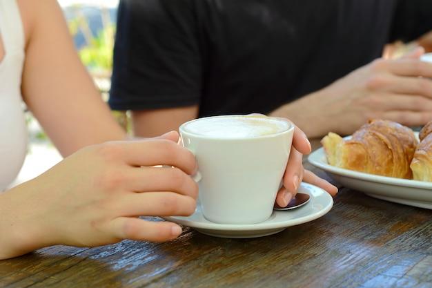 Schließen sie herauf schuss der heißen kaffeetasse auf einer tabelle