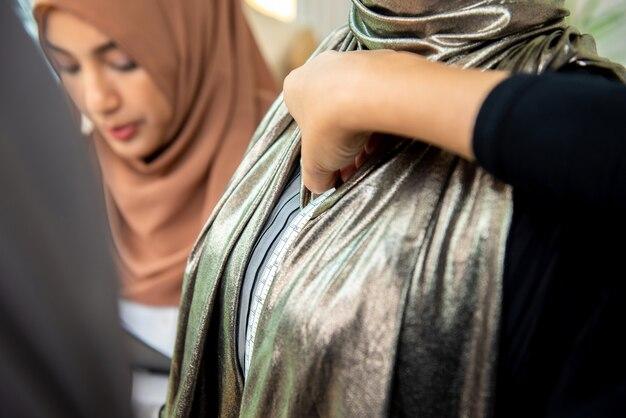 Schließen sie herauf schuss der moslemischen weiblichen schneiderhand unter verwendung eines messenden bands