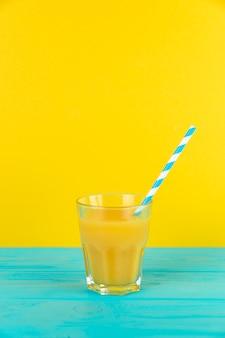 Schließen sie herauf schuss des frischen orangensaftglases mit gelbem hintergrund