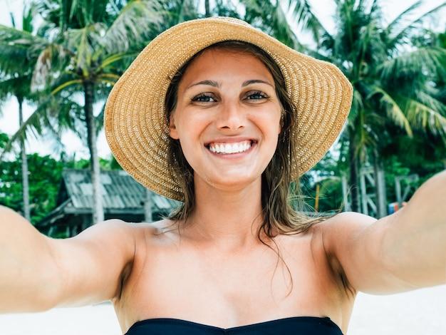 Schließen sie herauf schuss des glücklichen lächelnden weiblichen touristen. posen für selfie