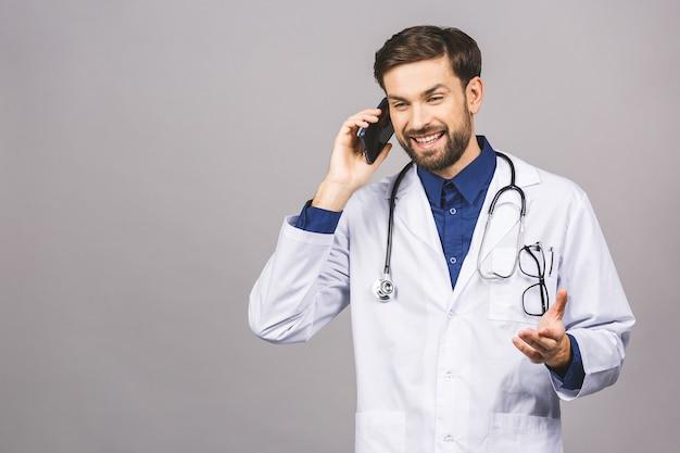 Schließen sie herauf schuss des gutaussehenden mannarztes lokalisiert auf grauem hintergrund, der auf smartphone spricht, positiv lächelnd