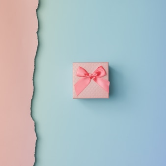 Schließen sie herauf schuss des kleinen geschenks, das mit rosa band auf rosa blaue wand gewickelt wird. minimales konzept. flach liegen. draufsicht.