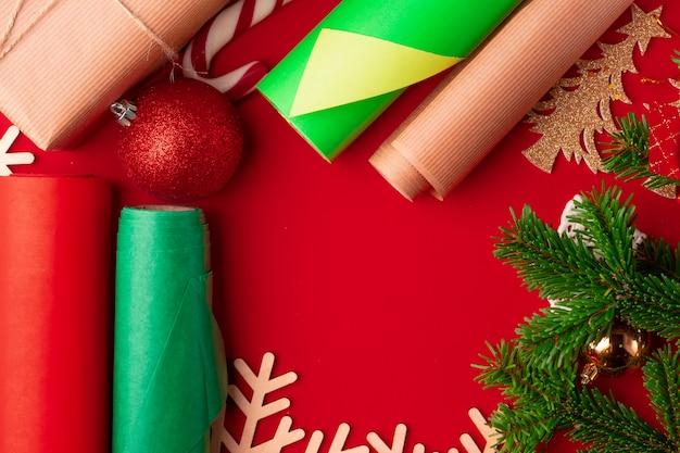 Schließen sie herauf schuss des packpapiers und der einzelteile für das weihnachten, das auf rot verziert