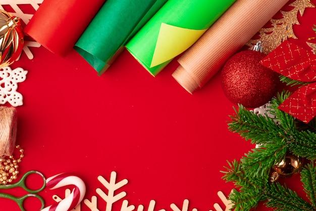 Schließen sie herauf schuss des packpapiers und der einzelteile für das weihnachten, das auf rotem hintergrund verziert