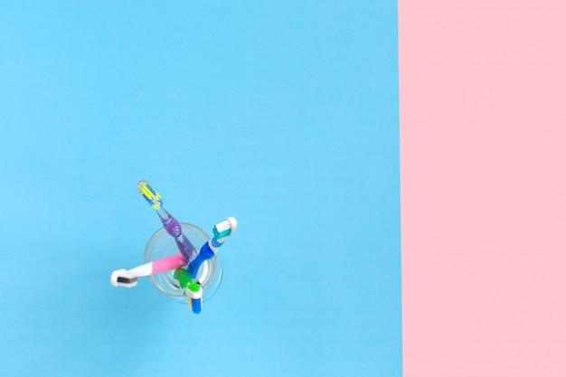 Schließen sie herauf schuss des satzes mehrfarbiger zahnbürsten in einem glas auf farbhintergrund