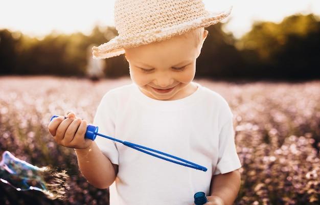 Schließen sie herauf schuss eines glücklichen kindes, das seifenballons im freien gegen sonnenuntergang tut. kleiner süßer junge, der beim spielen im freien lächelt.
