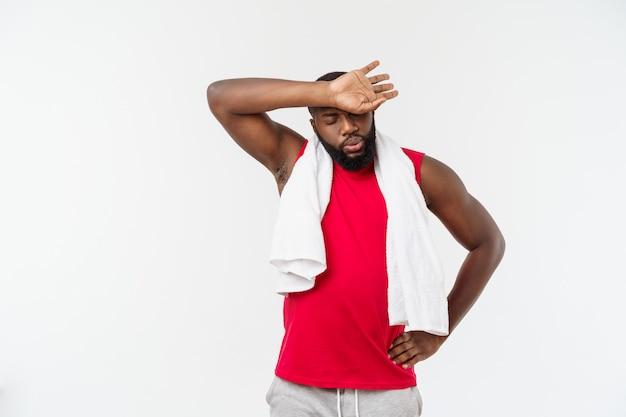 Schließen sie herauf schuss eines traurigen müden afroamerikanermannes in der sportkleidung, die sein gesicht mit einem weißen tuch, auf weiß abwischt