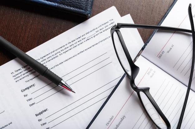 Schließen sie herauf schuss von brillen auf dokumentenpapieren