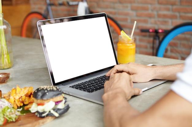 Schließen sie herauf schuss von den händen des mannes auf der tastatur des offenen generischen laptops. männlicher student, der online auf seinem notebook studiert