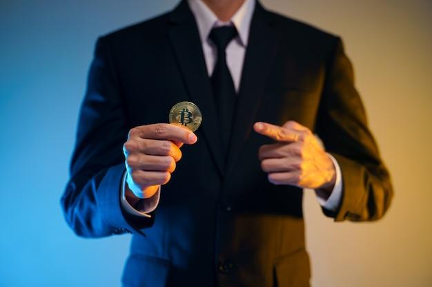Schließen sie herauf schuss von geschäftsmann im schwarzen anzug, der goldene münze lokalisiert auf hintergrund hält.