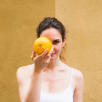 Schließen sie herauf schussfrauen-bedeckungsgesicht mit orange