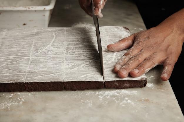 Schließen sie herauf schwarze mannhände, die scheibe frisch gebackenen schokoladenkuchens auf marmortisch in professioneller handwerklicher süßwaren schneiden