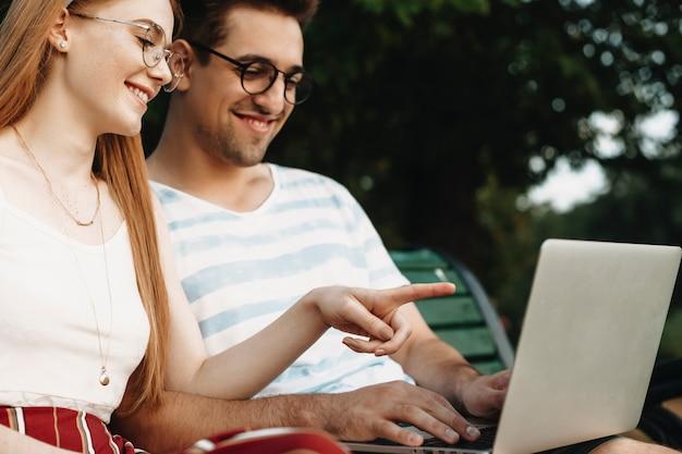 Schließen sie herauf seitenansicht einer frauenhand, die auf einen bildschirm eines laptops zeigt, der lächelt, während ihr freund laptop hält und draußen im park lachend schaut.