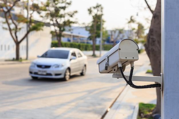 Schließen sie herauf sicherheits-überwachungskamera, die auf der straße arbeitet und vom auto verwischt ist