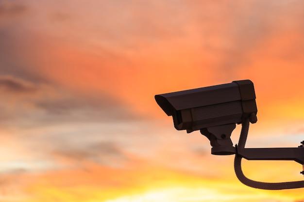 Schließen sie herauf sicherheits-überwachungskamera mit schönem sonnenunterganghintergrund