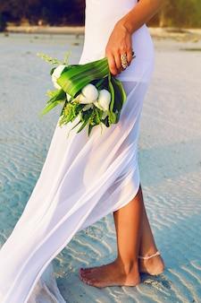 Schließen sie herauf sinnliches modebild ow frau im weißen kleid, das schönen weißen lotusstrauß hält.