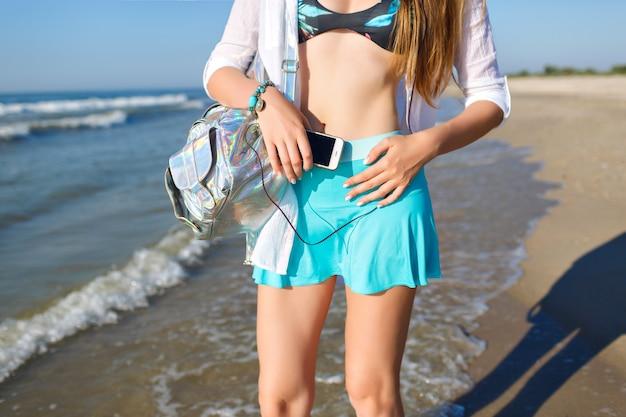 Schließen sie herauf sommer-modedetails, junge frau, die am strand aufwirft, geek-details, telefon halten und musik hören, stilvolle helle strandkleidung tragen, nahe ozean aufwerfen.