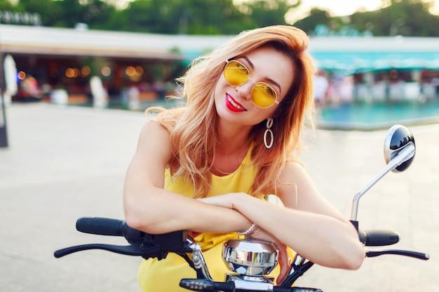 Schließen sie herauf sommerporträt der fröhlichen rothaarigen frau in der stilvollen gelben sonnenbrille, die elektroroller in der sonnigen modernen stadt reitet. trendige accessoires.