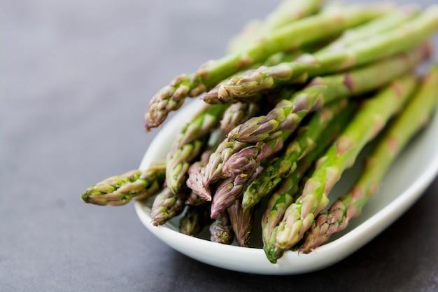 Schließen sie herauf spargelstangen über dunklem hintergrund mit kopienraum. gesundes, veganes lebensmittelkonzept. sauberes essen.