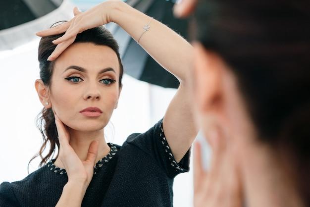 Schließen sie herauf spiegelreflexion der brünetten frau mit blauen augen und nacktem make-up im kleinen schwarzen kleid.
