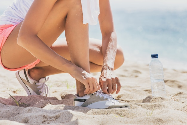 Schließen sie herauf sportliche frau, die ihre schnürsenkel am strand bindet