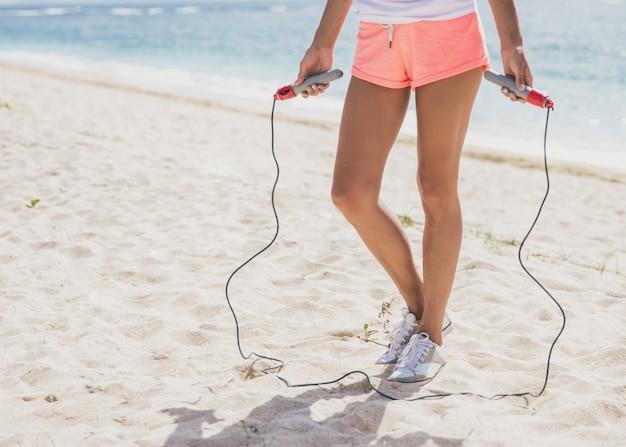 Schließen sie herauf sportliche frau, die springseil am strand hält