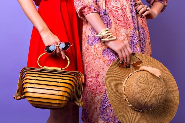 Schließen sie herauf stilvolle modedetails, zwei frau mit hellen kleidern, die am lila hintergrund aufwerfen, strohhut der sonnenbrille und super trendige moderne hölzerne handtasche halten.