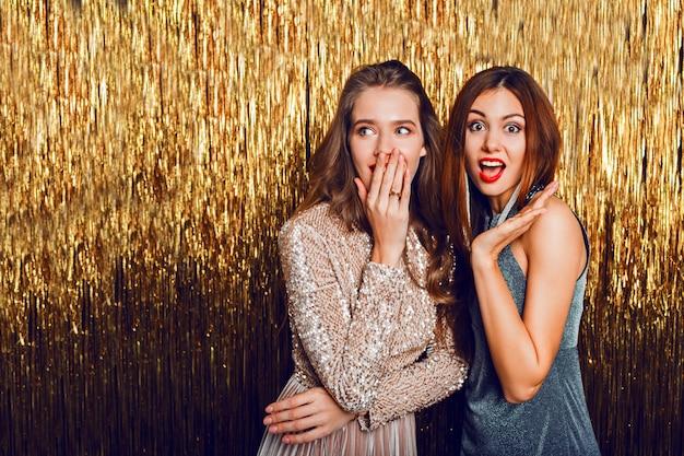 Schließen sie herauf studio bild von zwei erstaunlichen sexy feiernden mädchen mit roten lippen, überraschungsgesicht,