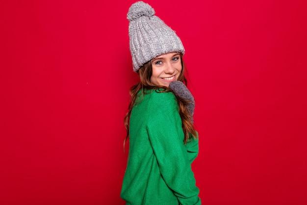 Schließen sie herauf studio-porträt der glücklichen entzückenden jungen dame, die graue wintermütze und grünen pullover aufwirft und lächelt