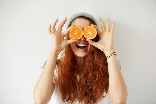 Schließen sie herauf studio-porträt der jungen lächelnden frau, die hälften der orangen an ihren augen hält