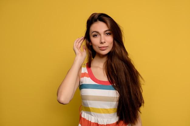 Schließen sie herauf studio-porträt der schönen kaukasischen frau mit dem langen dunklen haar, das gestreiftes kleid aufwirft