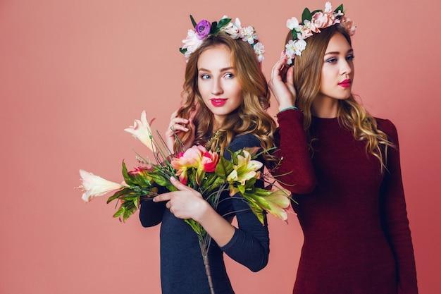 Schließen sie herauf studio-porträt von zwei jungen hübschen blonden frauen im frühlingsblumen-zorn, erstaunliche gewellte lange frisur, helles schminken, blick auf kamera.