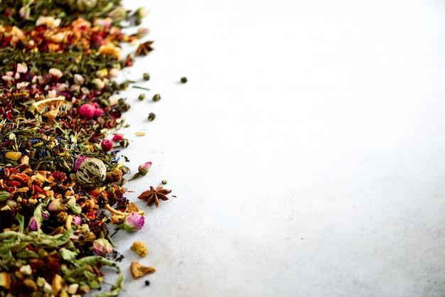 Schließen sie herauf teehintergrund: grün, schwarz, mit blumen, kräuter-, minze, melisse, ingwer, apfel, rose, limettenbaum, früchte, orange, hibiskus, himbeere, kornblume, moosbeere.